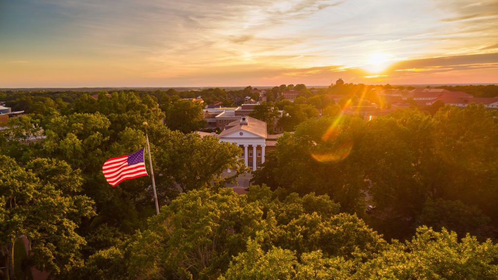 Arial view of the University of Mississippi Lyceum with a United States flag shown blowing in the breeze
